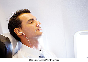 tired businessman listening music and relaxing on airplane