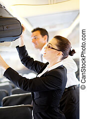 friendly flight attendant helping passenger with carry on...