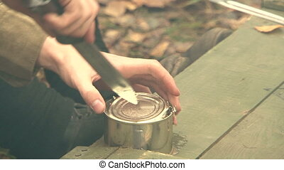 Opening a tin can with a knife