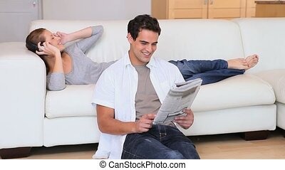 Woman listening to music while her husband reads the newspaper