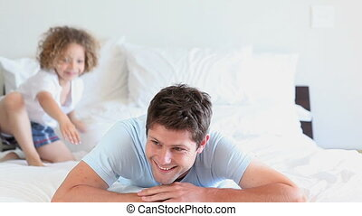 Boy jumping on his father back who's lying on his bed
