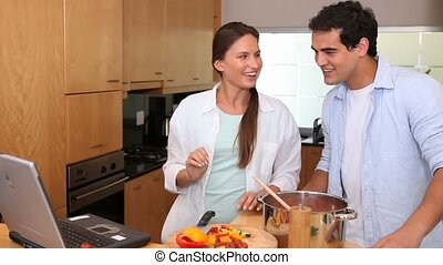 Laughing couple looking a recipe on a laptop in a kitchen