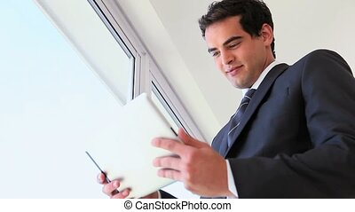 Man in suit using a touchpad near a window
