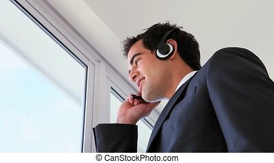 Man looking outside while calling with a headset - Low-angle...
