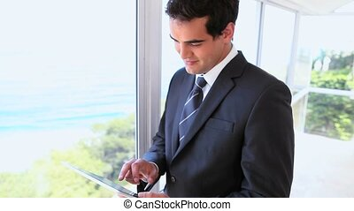 Man in suit using a tablet computer while standing in a...