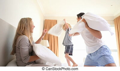 Young family having a pillow fight in the parents room