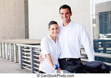 happy young couple pushing luggage trolley at airport