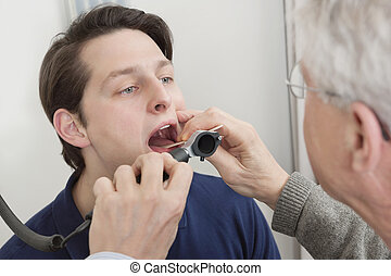 Throat Exam With Depressor - Young man getting his throat...