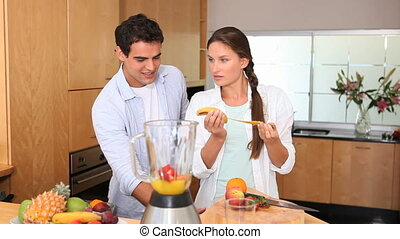 Woman putting a banana in a blender with her husband next to...