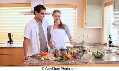 Woman feeding her husband a tomato in the kitchen