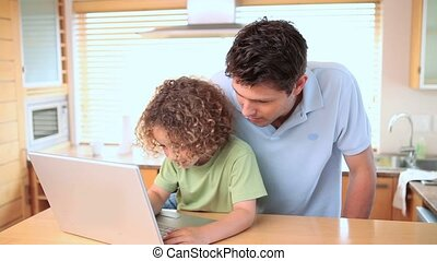 Boy looking at a laptop screen with his father - Boy looking...