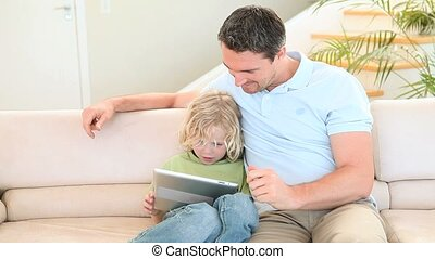 Father and son sitting on a cough while using an ebook