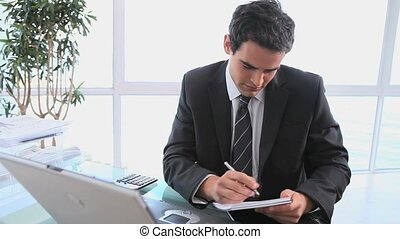 Businessman writing on a sheet while looking at his laptop