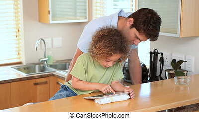 Boy using a ebook with his father in the kitchen