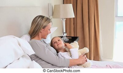 Mother hugging her daughter in a bed