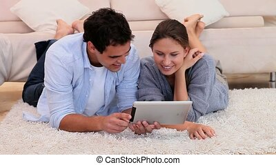 Couple using an tablet PC while lying on the living room...