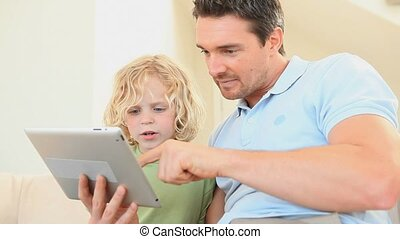 Father using an ebook with his son in the living room