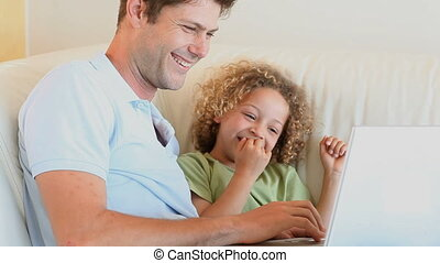 Father with his son on knees using a laptop in a living room