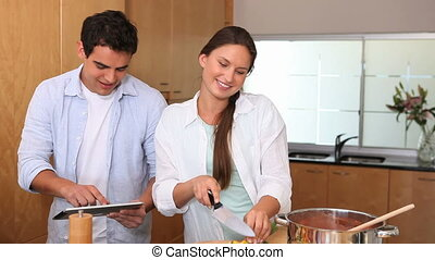 Woman cooking with her husband - Woman cooking while the...