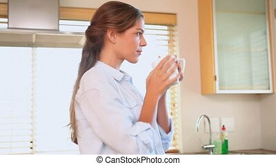 Woman drinking from a cup in her kitchen