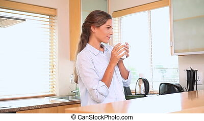 Woman holding a mug is thinking in a kitchen