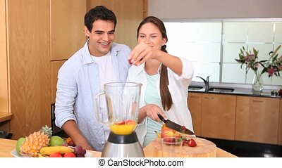 Woman adding fruits in a blender while her husband is...