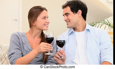 Couple toasting with glasses of wine in the living room