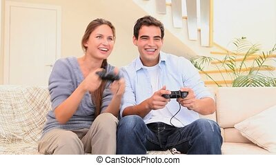 Couple playing a video game in the living room