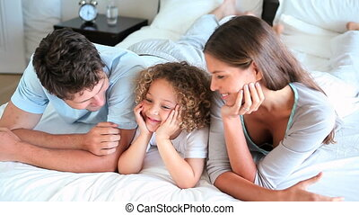 Child lying between his two parents in a bed