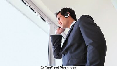 Businessman holding his headset microphone while calling