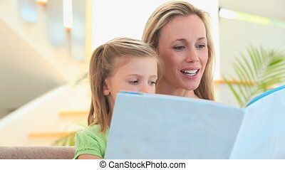 Mother reading a story to her blonde daughter