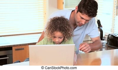Father showing his son how to use a laptop and a tablet
