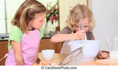 Little boy mixing a dough while his sister is helping in the...