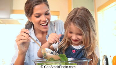 Little girl mixing salad with her mother in the kitchen