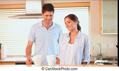 Couple drinking coffee in the morning in a kitchen