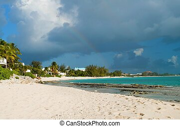 Rainbow Over Caribbean Beach - Gathering rain clouds over a...