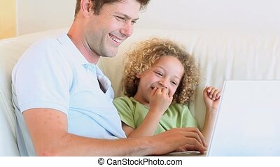 Happy father is teaching to his son how to use a laptop in a...