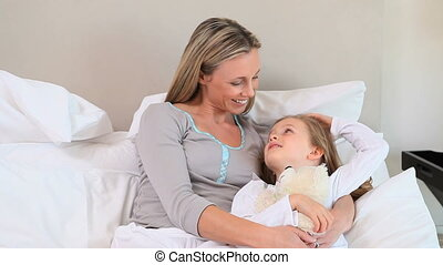 Mother and daughter in a bed waving hands