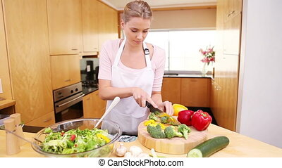 Woman preparing a salad with peppers in her kitchen