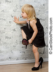 The little girl measures the mother's shoes with heels...