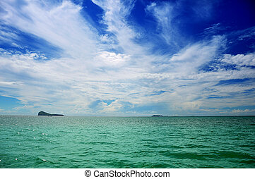 Blue sky and ocean - Blue sky with clouds and green ocean