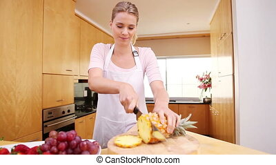 Young lady cutting a pineapple in her kitchen