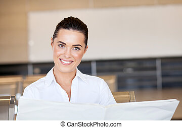 businesswoman reading newspaper at airport