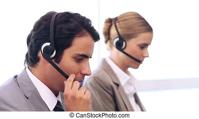 Call centre workers talking on headset in a bright room