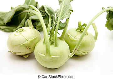 Kohlrabi with stem and leaves on white background