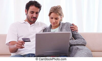 Couple using a credit card while sitting with a laptop