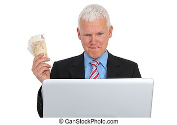Businessman with Bills and Laptop on Sofa