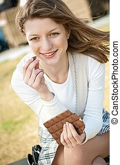 Young woman eating chocolate - Lifestyle outdoor Young...