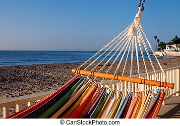 Striped Hammock In Front Of Ocean - Colorful stripy hammock...
