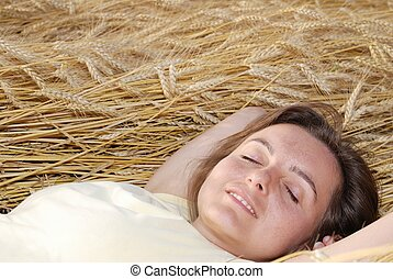 Young woman lies in golden grain - Young cheerful dreaming...